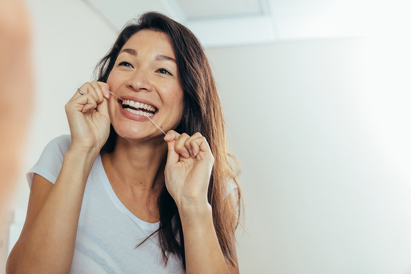Woman flossing and smiling