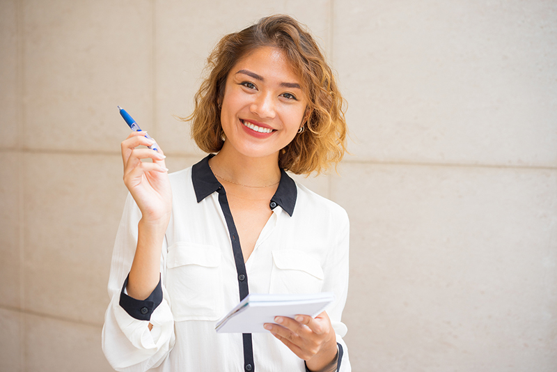Woman smiling taking notes