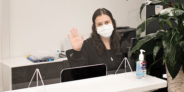 Woman waving white surgical mask and long dark hair.