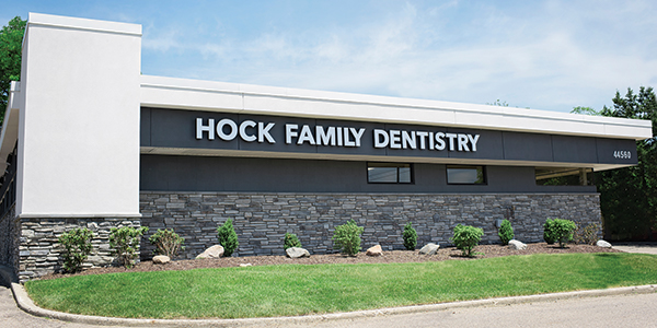 "Outdoor photo of building with gray brick, green grass, and bushes with sign that says ""Hock Family Dentistry"""