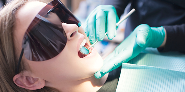 Young woman with protective dark glasses having dental work performed.
