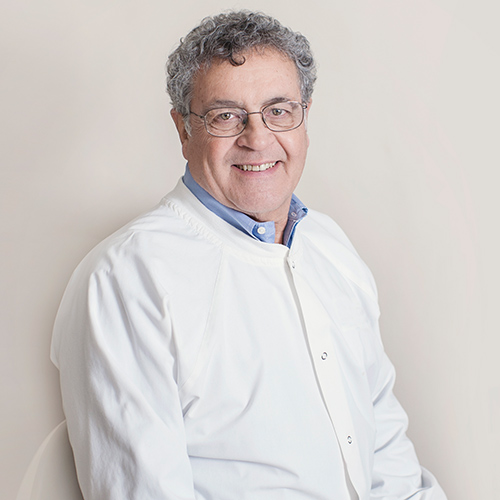 Portrait of a man with short curly gray hair, glasses, and a white shirt.