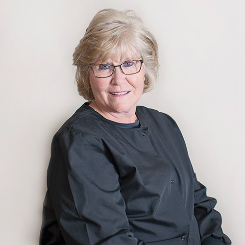Portrait of smiling woman with short blond hair, glasses, and black shirt.