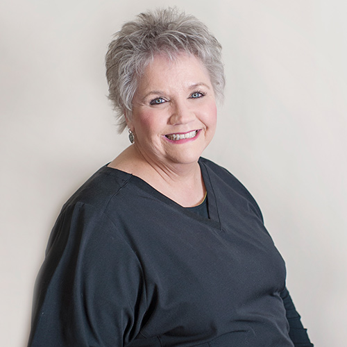 Portrait of smiling woman with short gray hair and black shirt.