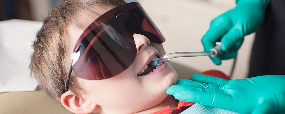 Picture of a young boy wearing dark eye shields with a suction tube in his mouth.