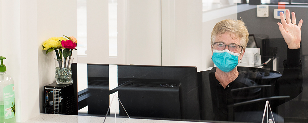 Woman waving while wearing glasses and a surgical mask seated at a computer behind a protective shield.