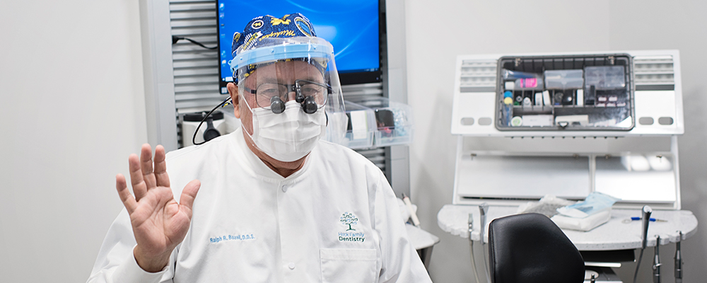 Portrait of a man with surgical face mask and face shield on with dental equipment in the background.