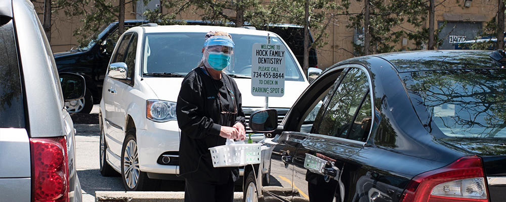 Woman in scrubs, surgical mask, and face shield standing outside of a black car.