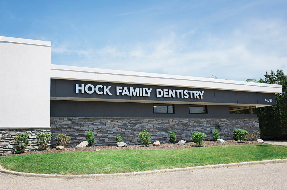 """Outdoor photo of a building with gray brick and a sign that says """"Hock Family Dentistry"""""""