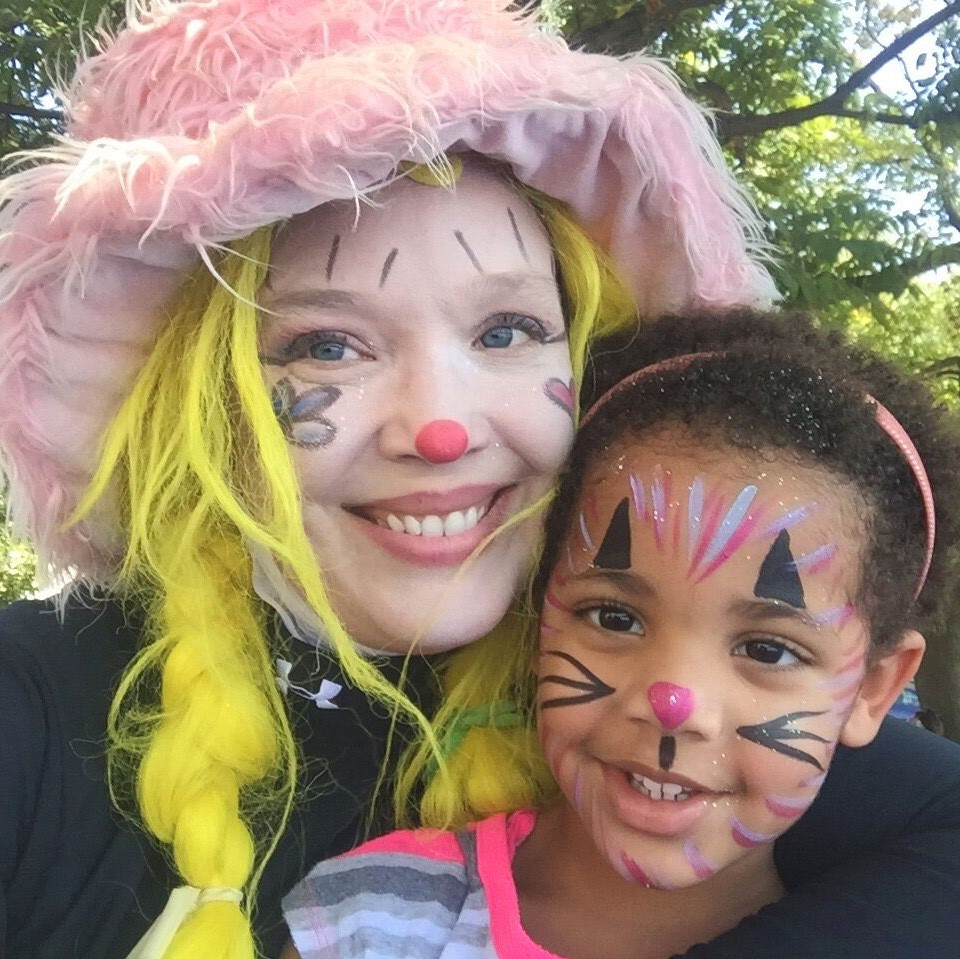 Corky Magic displaying her face painting with little girl with face painted like a cat