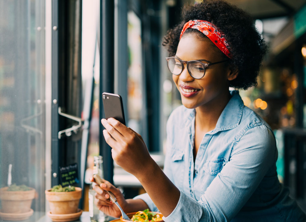Attractive young African woman smiling and reading texts on a cellphone while sitting alone at a counter in a cafe enjoying a meal