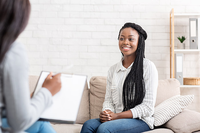 Positive results of therapy. Happy african american woman sitting at psychologist office after successful session, free space