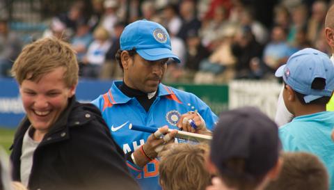 Sachin Tendulkar autographing a miniature cricket bat for a young fan