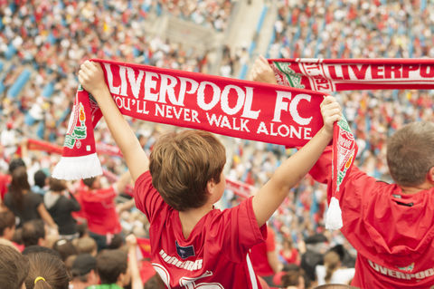 Fans holding up the Liverpool FC Flags at a Liverpool game.
