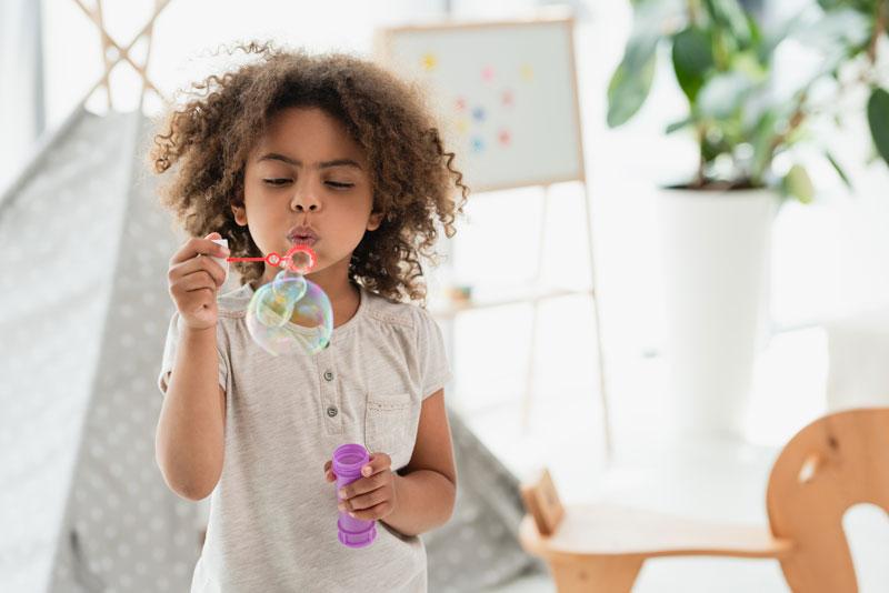 black female child blowing bubbles