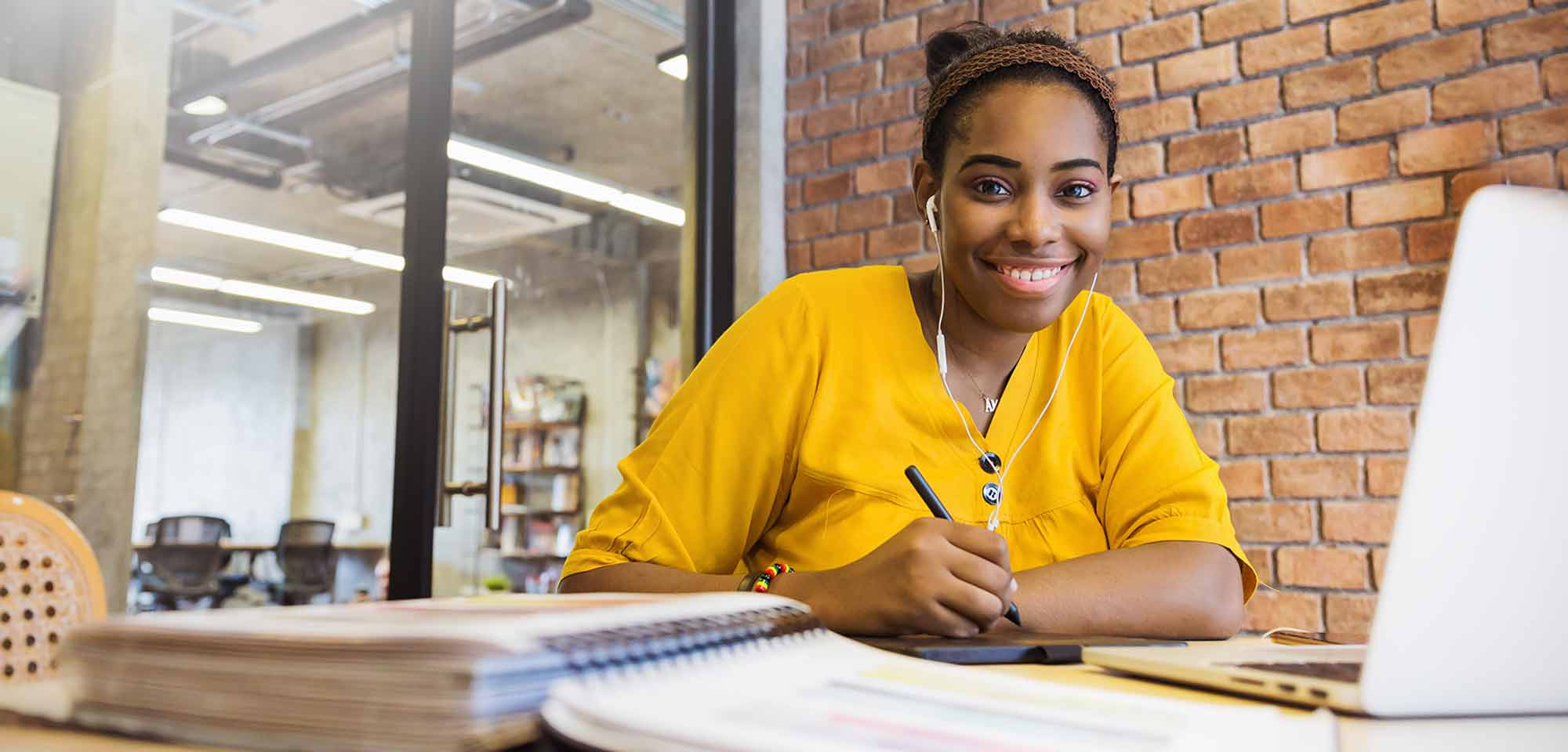 black female student wearing yellow shirt holding pen in front of laptop and books