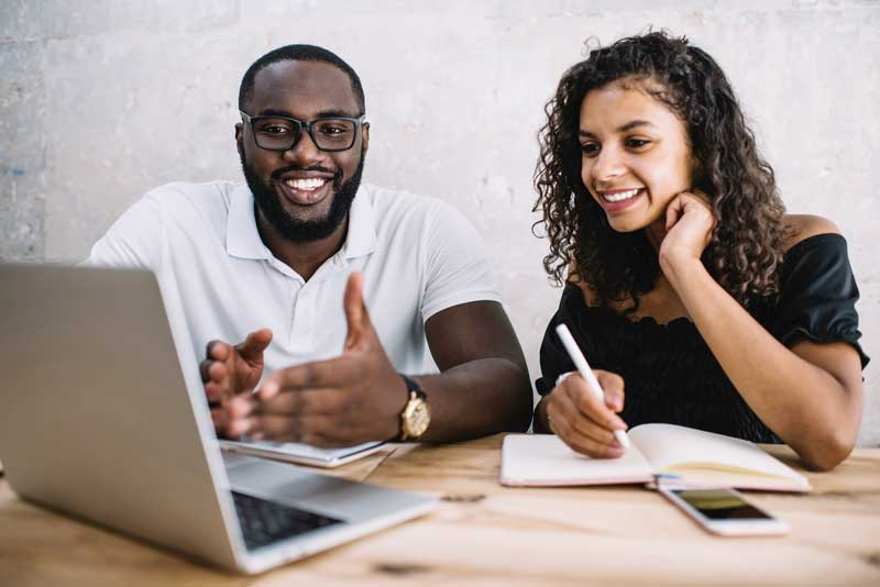 black man and woman working together in front of a laptop