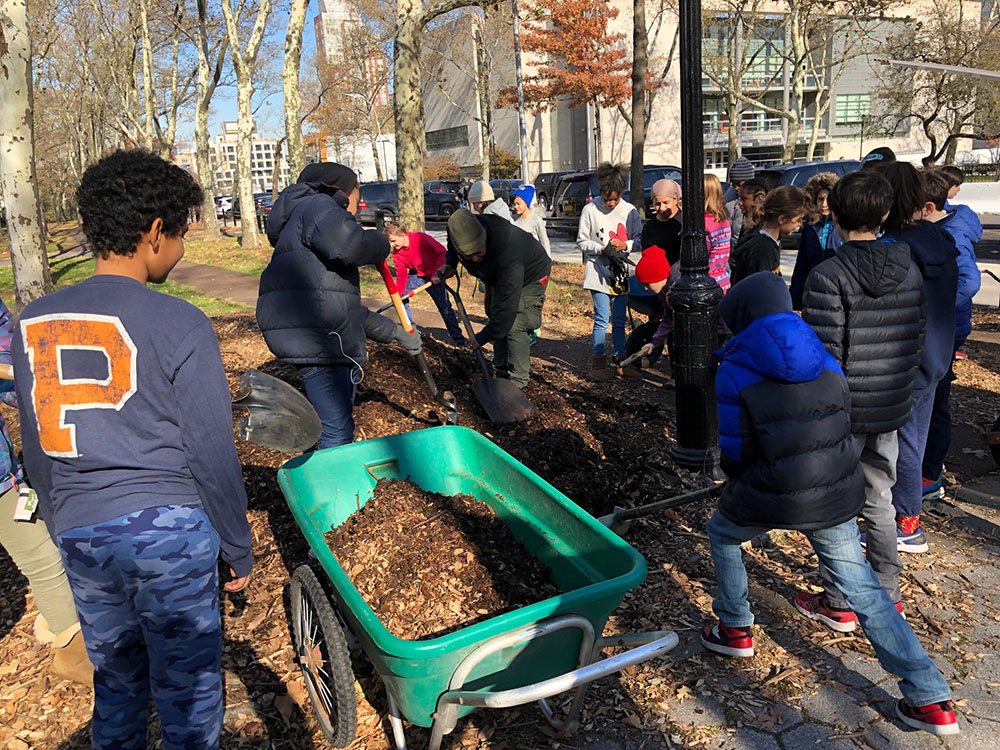 several kids around a wheel barrel filled with planting soil