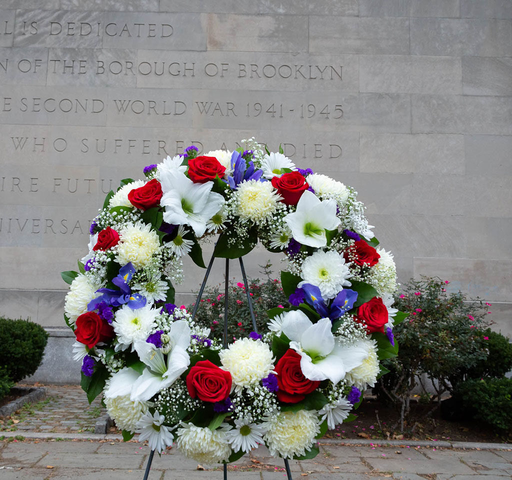 a red and white flower memorial wreath