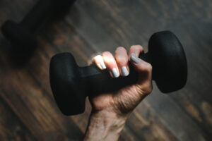 hand with painted gray nails holding dumbbell