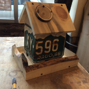 Bird house made from wood and license plates.