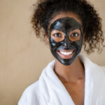 Smiling young woman with charcoal face mud looking at camera isolated on beige background with copy space. Portrait of african woman with curly hair wearing white bath robe getting black purifying mask at spa. Happy girl feeling relaxed at salon after face beauty facial treatment with peeling scrub clay.
