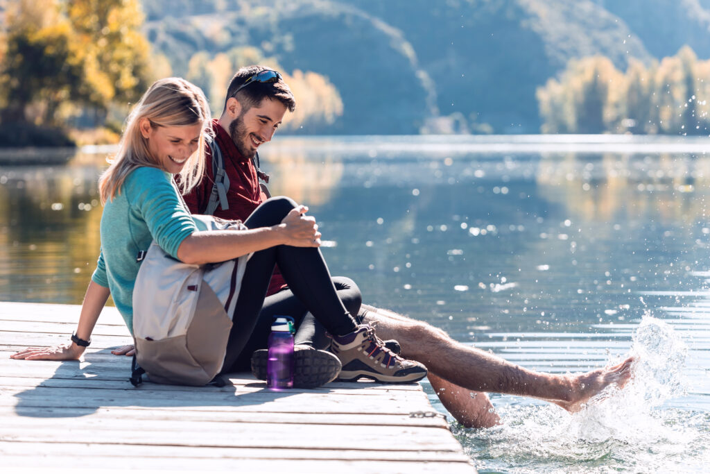 Couple sitting on a dock. Car City has quality used vehicles for your summer road trip up north.