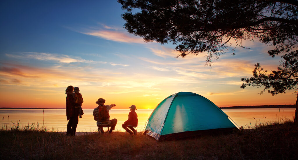 Family camping on a lake. Car City has quality used vehicles for your summer road trip up north.