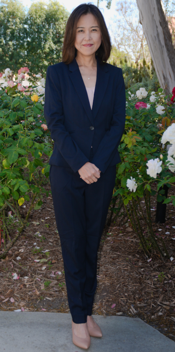 Photo of Asian female in a dark suit standing in front of flower bushes