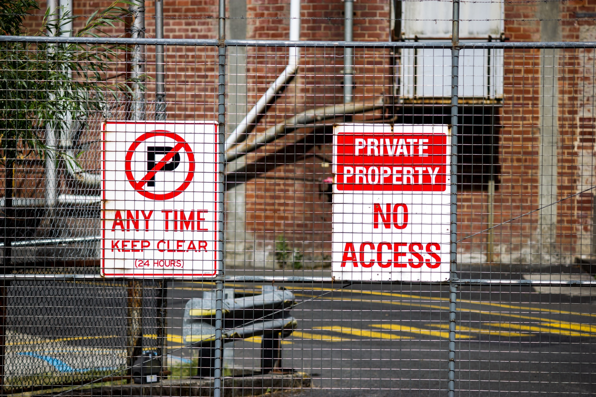 Photo of chain link fence with signs for private property and no parking attached