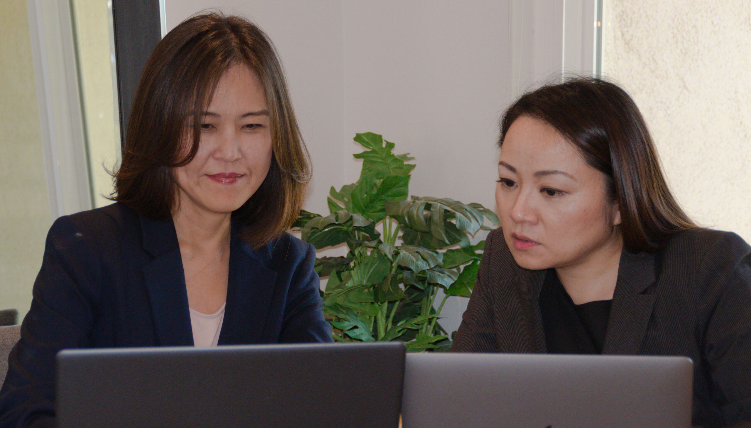 Two Asian females working on laptops