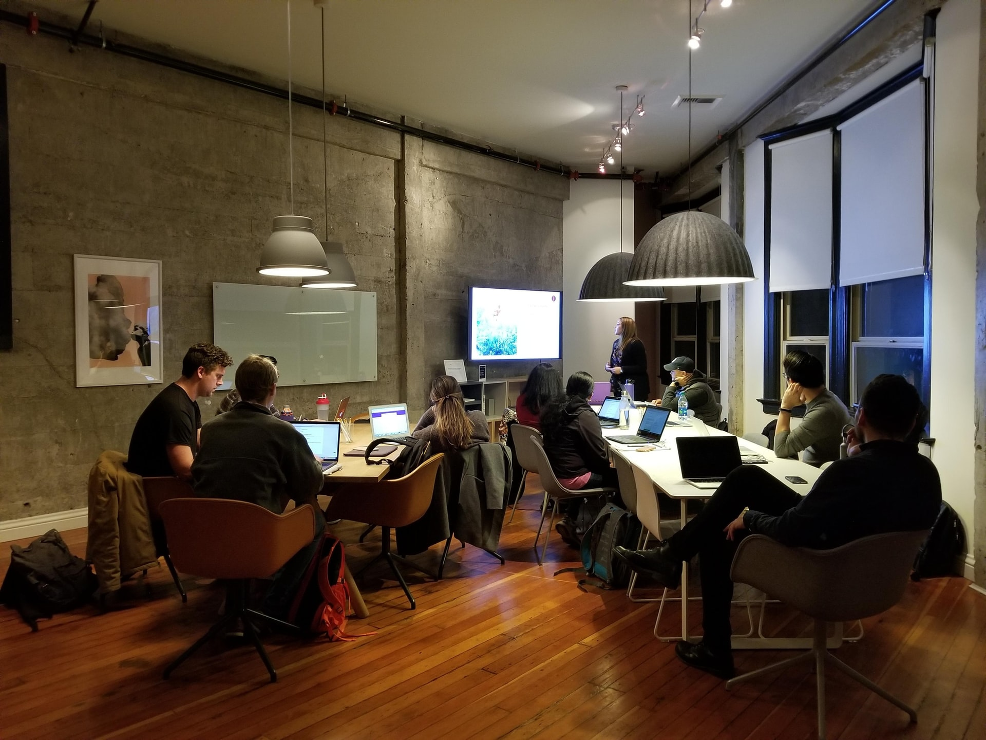 Photo of room with 10 people sitting around two tables working on their laptops