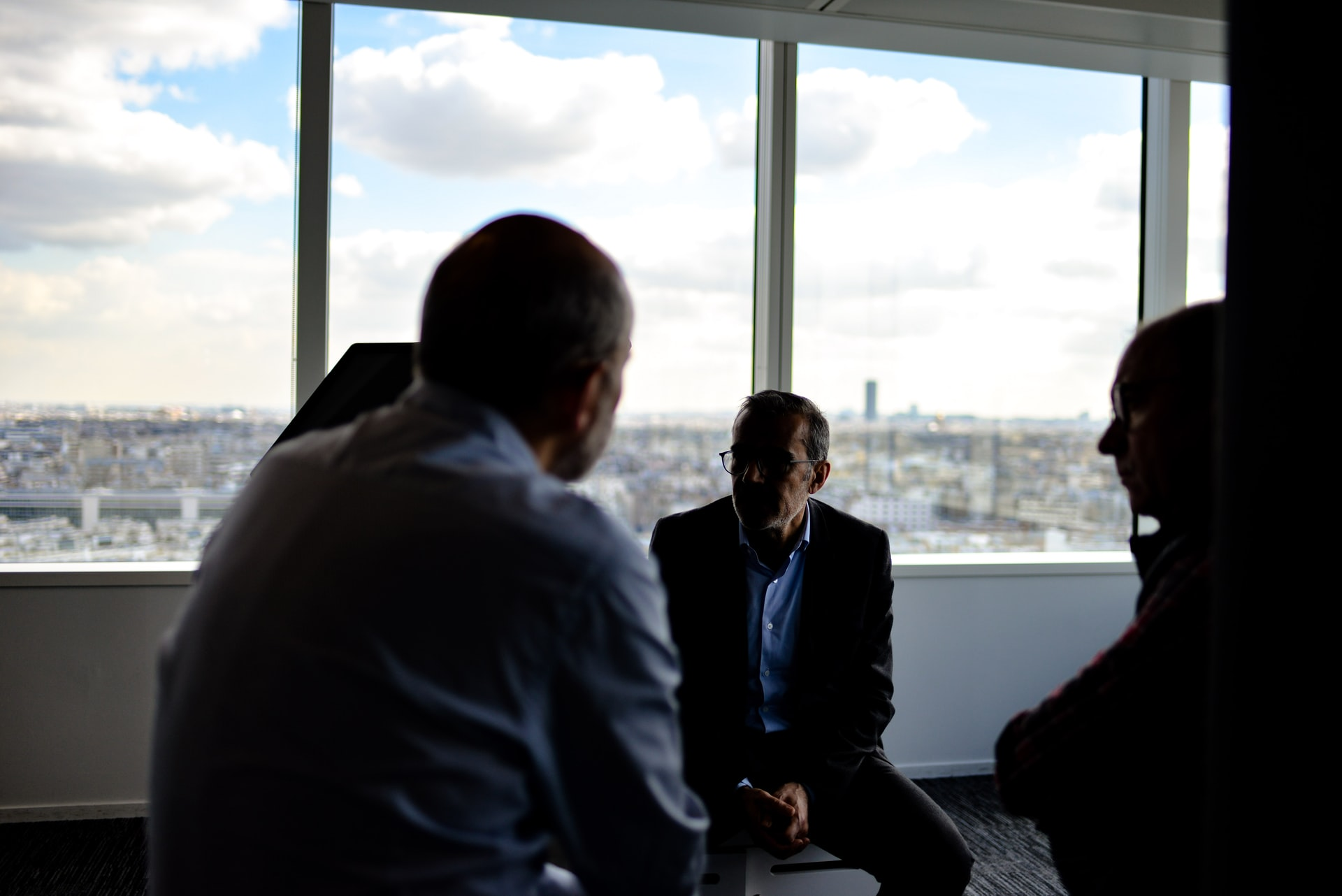 Photo of three middle aged white men sitting around in an office with a view
