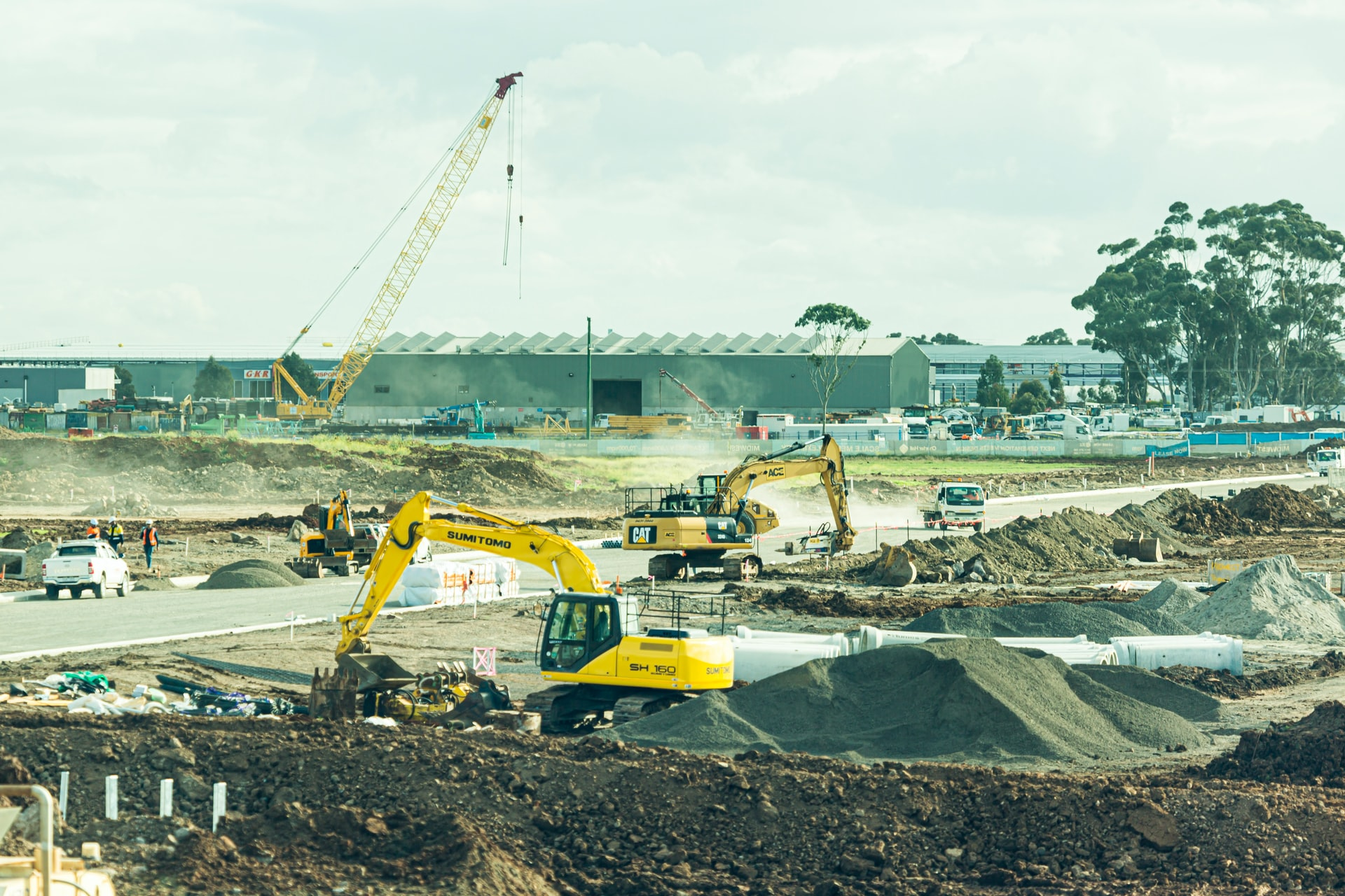 Photo of a construction site with large heavy equipment and dirt piles