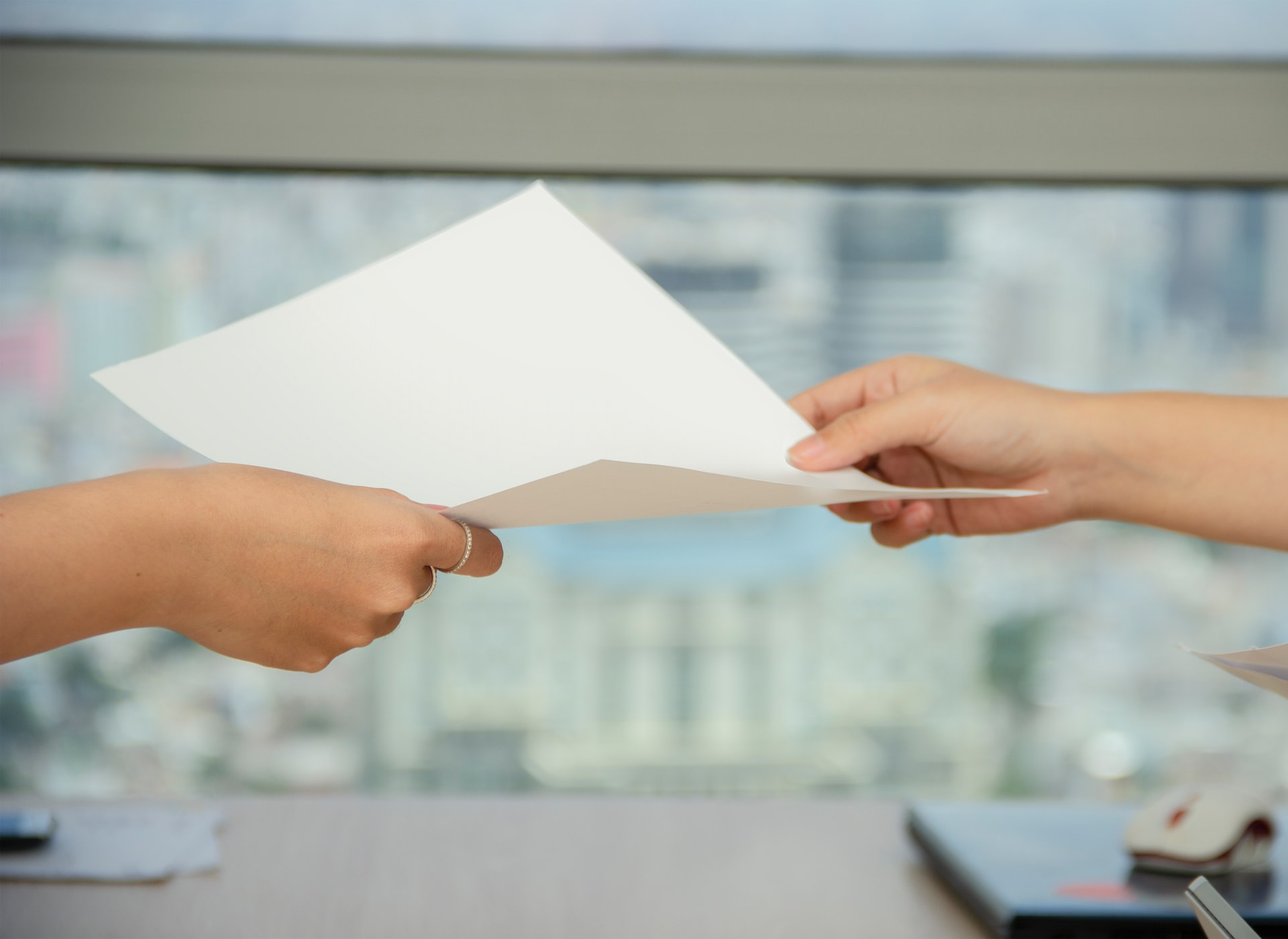 Photo of two females' hands holding a blank piece of paper