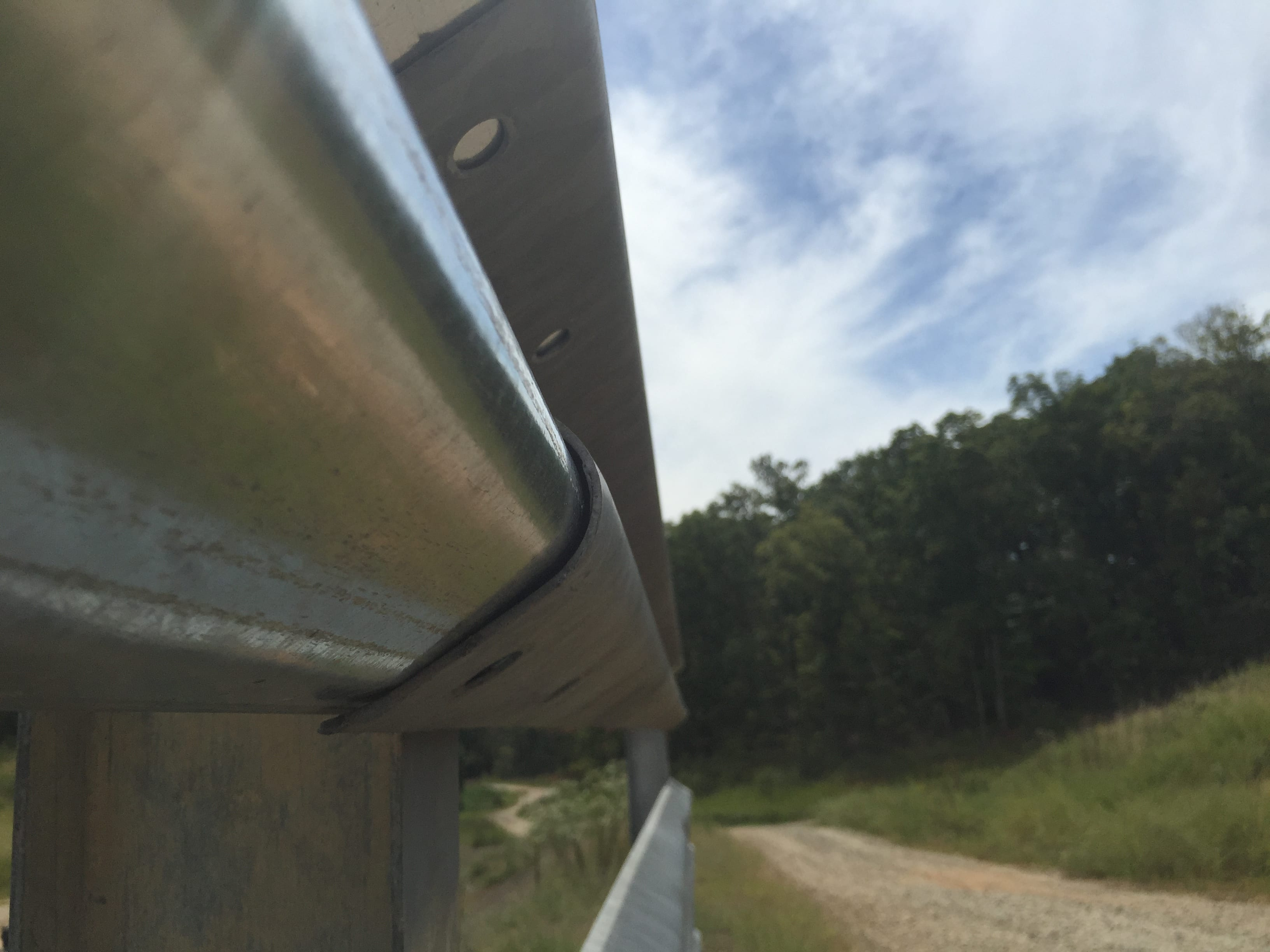 Looking down the length of a used and new highway guardrail overlap where the strength of the ribbon is displayed
