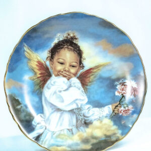 collectible plate with giggling cupid, closeup