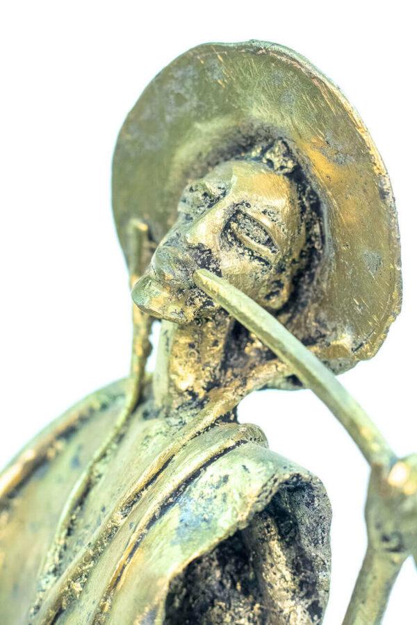 figurine, brass man with pipe, closeup