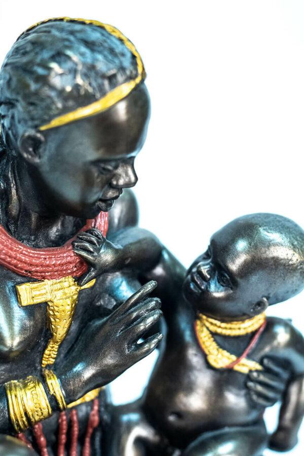 figurine, himba lady feeding her baby, closeup