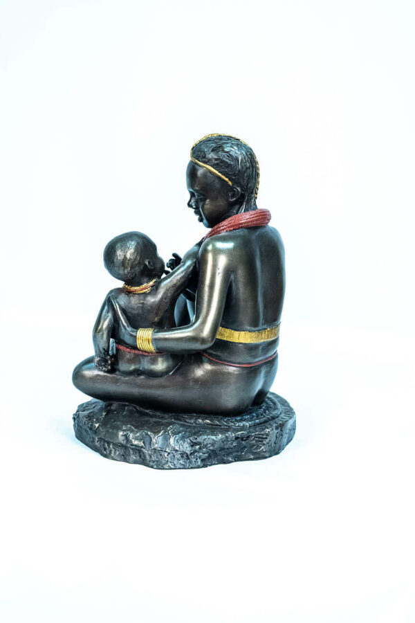 figurine, himba lady feeding her baby, left