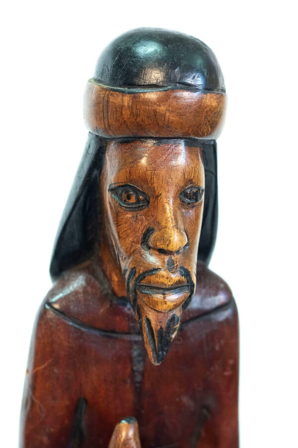 wood carving of man with beard holding gourd offering, closeup