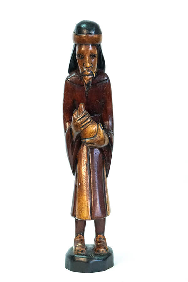 wood carving of man with beard holding gourd offering, front
