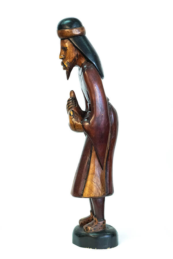 wood carving of man with beard holding gourd offering, left