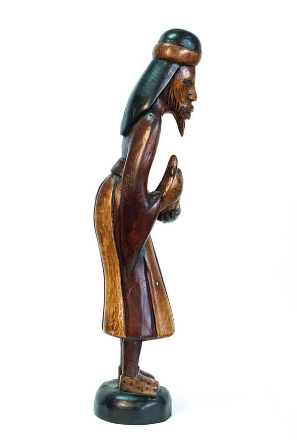wood carving of man with beard holding gourd offering, right