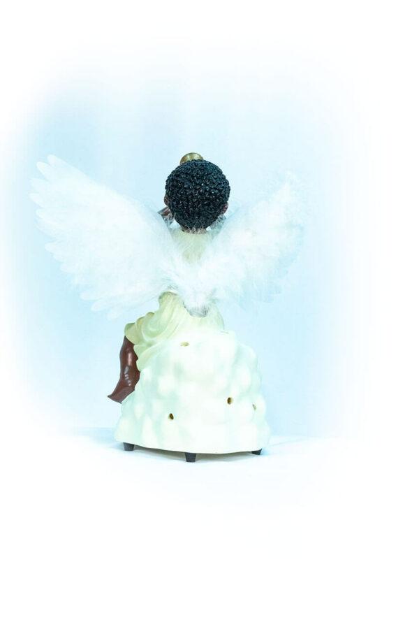 figurine, angel sitting on rock blowing horn, back