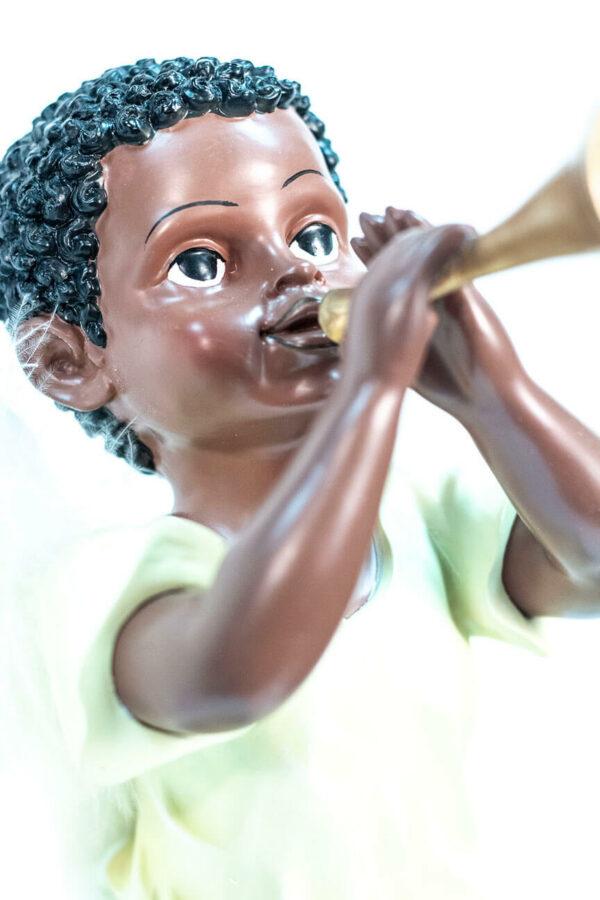 figurine, angel sitting on rock blowing horn, closeup