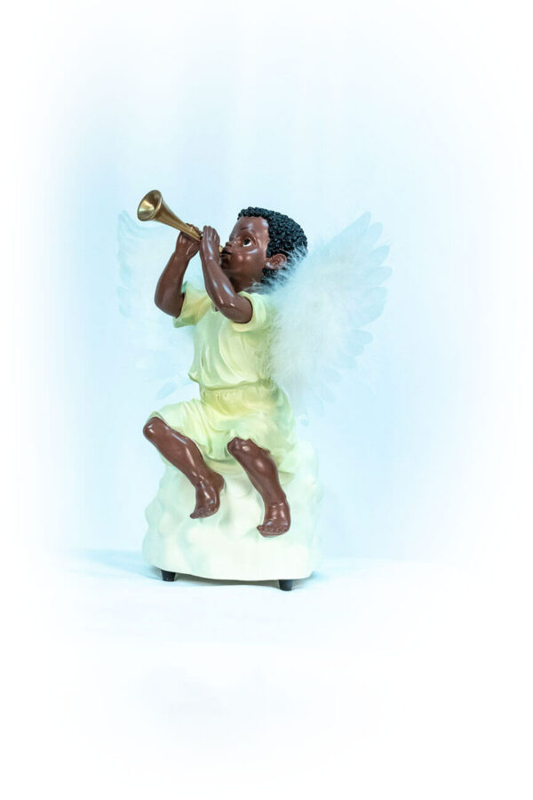 figurine, angel sitting on rock blowing horn, left