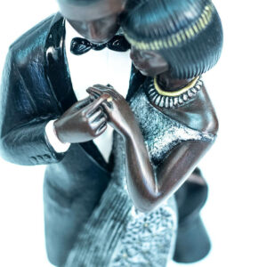 wedding couple figurine, bride and groom admire ring, closeup