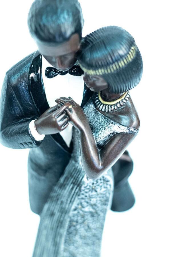 wedding couple figurine, bride and groom admire ring, closeup