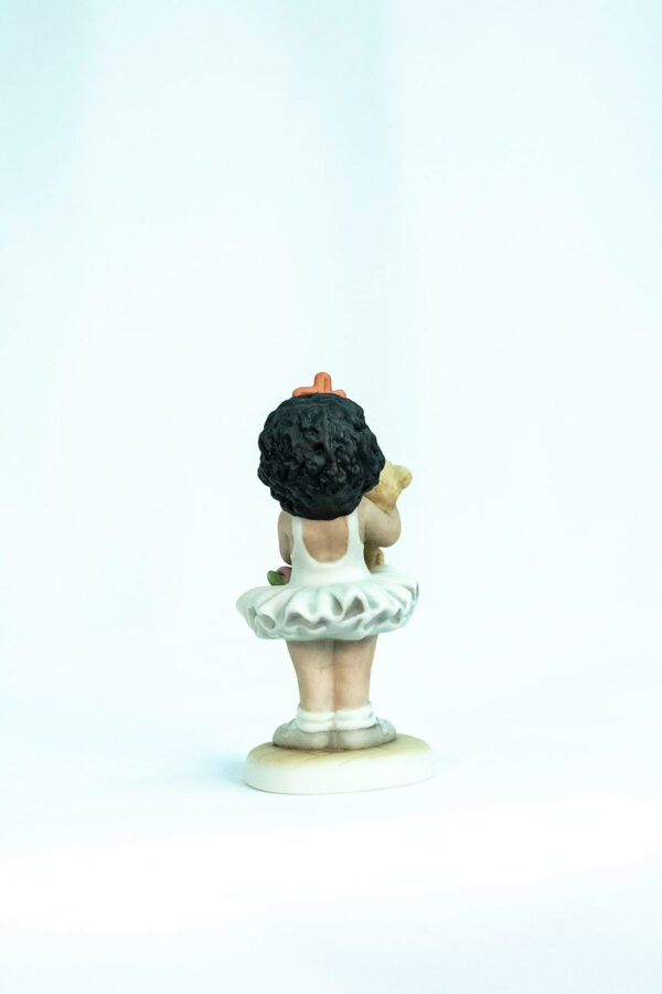 figurine, little girl holding teddy bear, back